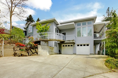 Large grey house exterior of modern home with large parking lot. Archivio Fotografico