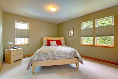 Large and bright room with bed for guests with many windows. Stock Photo