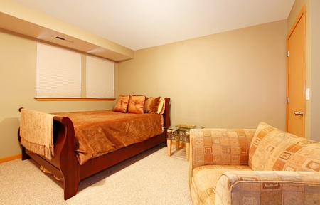 basement: Garden level simple guest bedroom with one single bed and large arm chair with green walls.