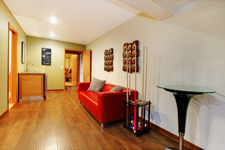 Home interior basement playy room hall way area with red sofa.  photo