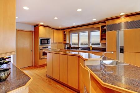 cucina moderna: Grande cucina in legno lusso moderno con ripiani in granito e pavimento in legno giallo. Archivio Fotografico
