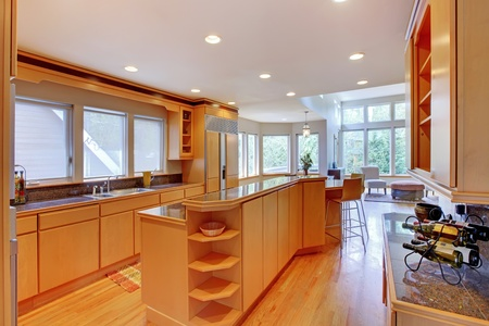 stainless steel kitchen: Large luxury modern wood kitchen with granite counter tops and yellow hardwood floor.