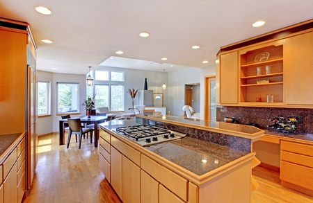 stove: Large luxury modern wood kitchen with granite counter tops and yellow hardwood floor.