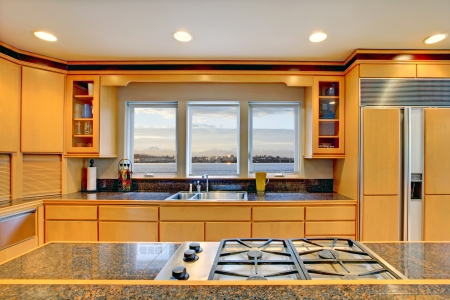 kitchen appliances: Large luxury modern wood kitchen with granite counter tops and yellow hardwood floor.
