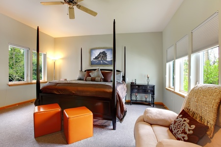Large bedroom with five windows and black post bed with brown bedding. Modern and classic comfortable design. photo