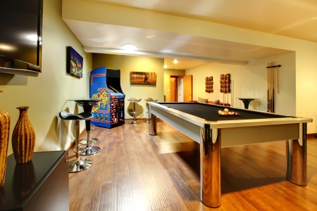 furnished: Fun play room home interior. Basement room without windows with pool table, TV, games. Stock Photo