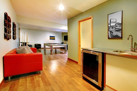 Fun play room home interior. Basement room without windows with pool table, TV, games. photo