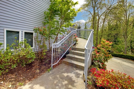Large grey house exterior of modern home with curved staircase leading to the front door. Stock Photo - 12621343