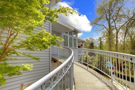 Large grey house exterior of modern home with curved staircase leading to the front door. Stock Photo - 12621334