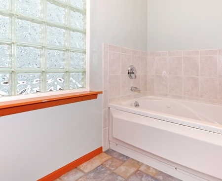 New bathroom corner with glass block window and tub with beige tile. photo
