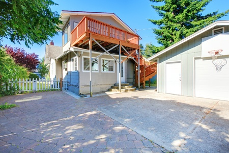 American old hoouse with a new large deck. View from the back yard with garage. Stock Photo