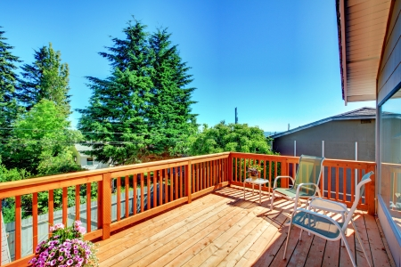 home exterior: Large new wood deck home exterior with chairs, trees and flowers. Stock Photo