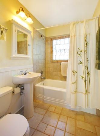 Small beige bathroom with walk in white shower and white cabinet. Archivio Fotografico