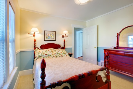 Beautiful romantic classic blue bedroom with red wood bed and dresser. photo