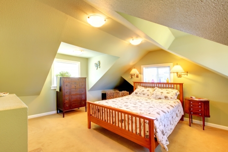 attic: Cozy attic bedroom with green walls and large bed.