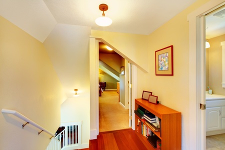 Hallway on the second floor of small  house with yellow walls.