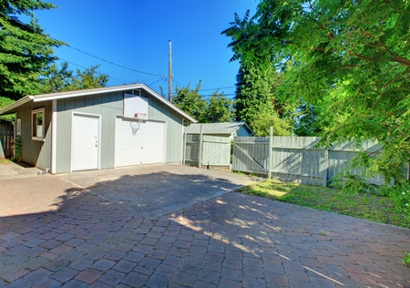 Large city back yard with garage and play or parking paved area. photo