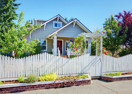 Grey small cute house with white fence and roses.