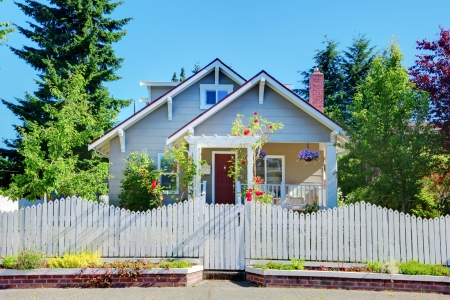 outside of house: Cute small grey old craftsman style house with white fence.