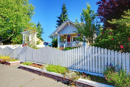 Charming old cute grey hosue behind the white fence with flowers. photo