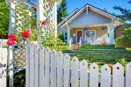 Craftsman: Charming old cute grey hosue behind the white fence with flowers. Stock Photo