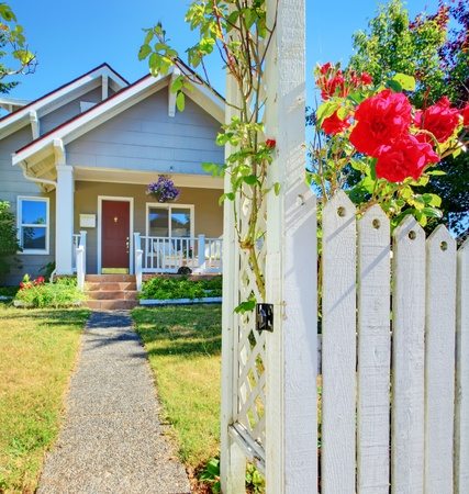 Small American house and white fece with red roses. photo