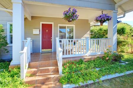 front porch: Gris casa de porche con puerta roja y barandas blancas.