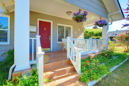Grey house porch with red door, white railings and purple flowers.