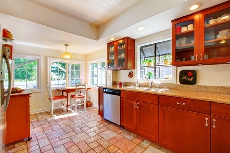 Cherry wood kitchen with tile floor and sunny table home interior. Stock Photo - 12621435
