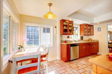 Cherry wood kitchen with tile floor and sunny table home interior. Stock Photo - 12621429