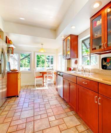 kitchen counter top: Cherry wood kitchen with tile floor and sunny table home interior.