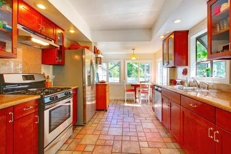 home appliances: Cherry wood kitchen with tile floor and sunny table home interior.