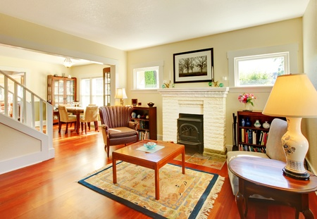 Beautiful sunny old living room with cherry floor and white fireplace. photo