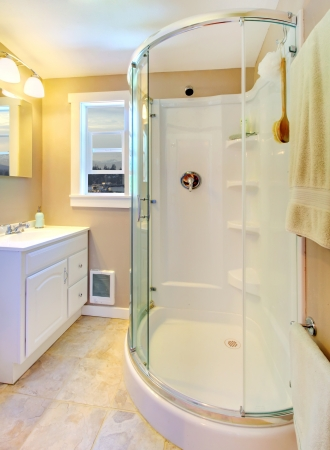 Small beige bathroom with walk in white shower and white cabinet. photo