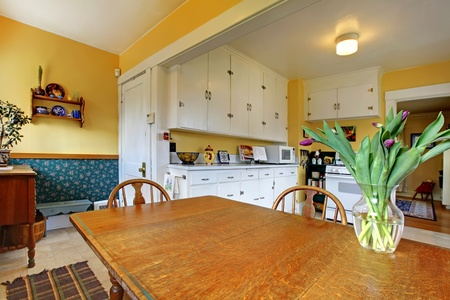 Old English charming kitchen with yellow walls and large table. photo