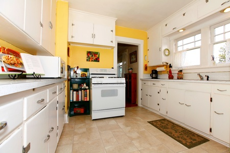 furniture design: White old small simple kitchen interior with yellow walls. Stock Photo