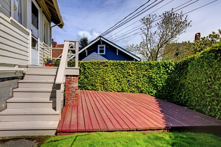 Small simple house with a small back yard deck. photo