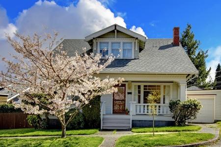 ribetes: Peque�a casa, blanca, con un �rbol en flor de cerezo y la hierba verde.