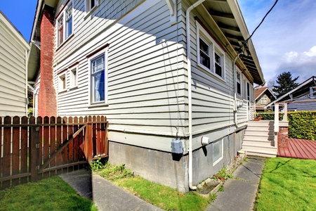Grey small old  house  corner with fence and back yard with deck. Stock Photo - 12621513