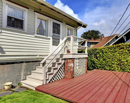 Corner of the grey old house with deck. Stock Photo - 12621494