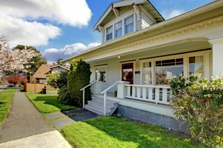 fachada de casa: Peque�a casa, blanca, con un �rbol en flor de cerezo y la hierba verde.