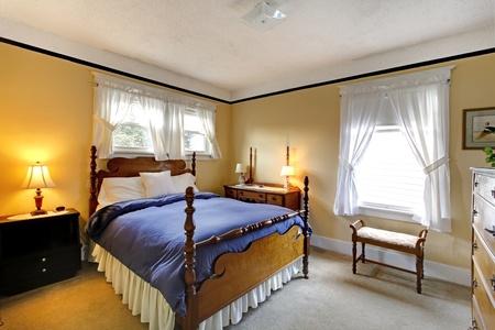 designers interior: Piccolo giallo accogliente camera da letto con la coperta blu e un design elegante.