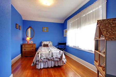 Bright blue kids bedroom in old English style with cherry hardwood floor and doll house. photo