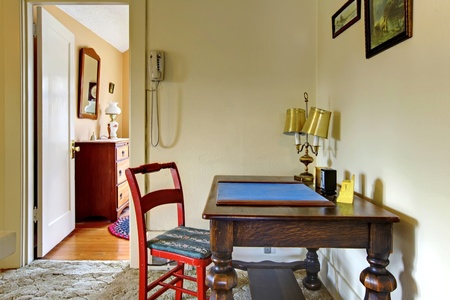 Home interior with old writing desk with red chair. photo