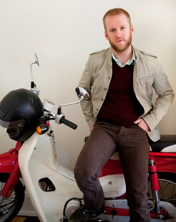 Young man is sittting on the white and red scooter bike indoors. photo