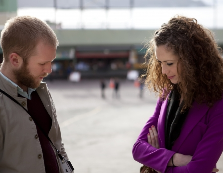 serious woman: Young couple talking on the street standing apart and looking down.