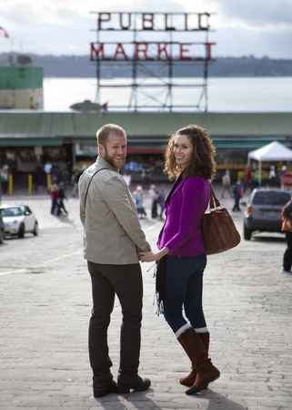 public market: Couple walking down to Pike Market, Seattle, WA. USA