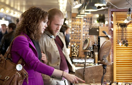 Young couple exploring and shopping indoor market. Pike Market. Seattle.