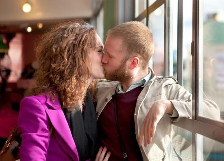 enamorados besandose: Pareja joven kisssing cerca de la ventana en el interior del edificio. Foto de archivo