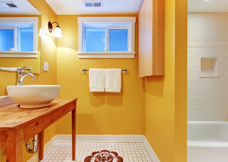 Orange bathroom with modern sink on the pine table with white tub. photo